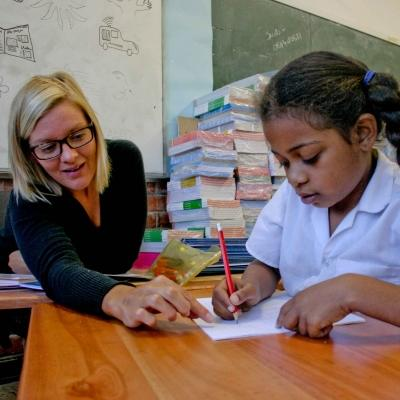 A student receives homework help from a volunteer working as a teacher in South Africa